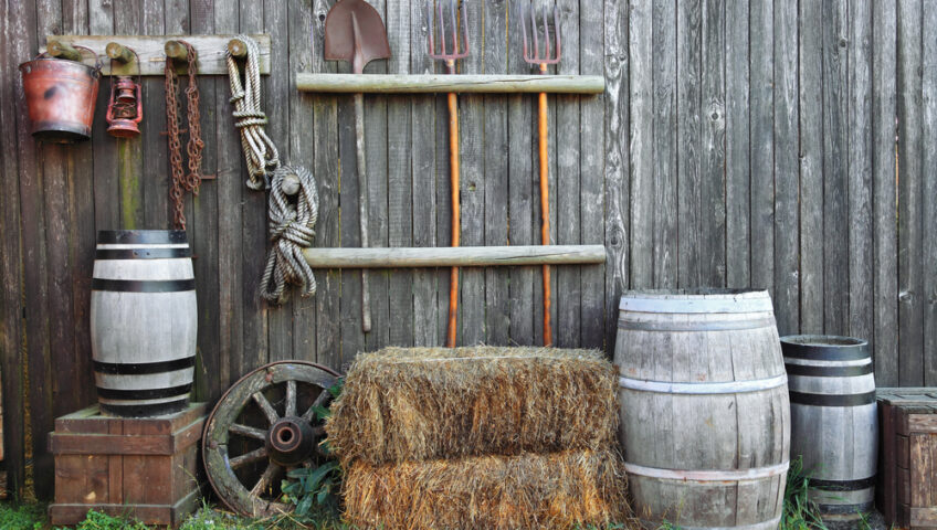 Various barrels, crates, wagon wheels, hay bales are propped up against the gray exterior wall of an old barn