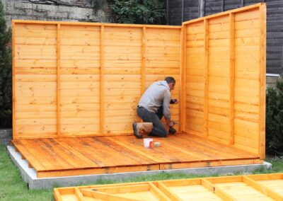 A worker assembles a wooden shed outside in their backyard. Only the floor and two walls of the shed have been put up. A third wall lies on the ground at the bottom of the photo, waiting to be lifted into place.
