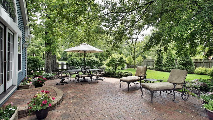 A brick patio outside of a blue house. On the patio, there are two lounge chairs with wheels and a table with an umbrella. Beyond the patio is a well-maintained lawn with several shrubberies and trees.