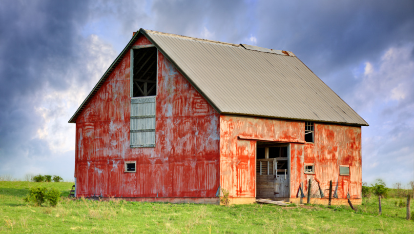 An old barn with faded paint in a grass field. The sky is cloudy with patches of blue in the background.