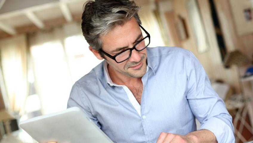 A businessperson wearing a blue button-up shirt and eyeglasses works on a tablet while flipping through a notebook at home.