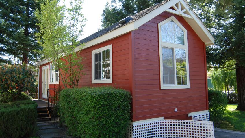 A small red house surrounded by tall trees and nicely-trimmed shrubberies.