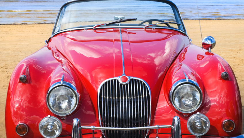 The front of a red vintage car with a dry sandy landscape in the background.