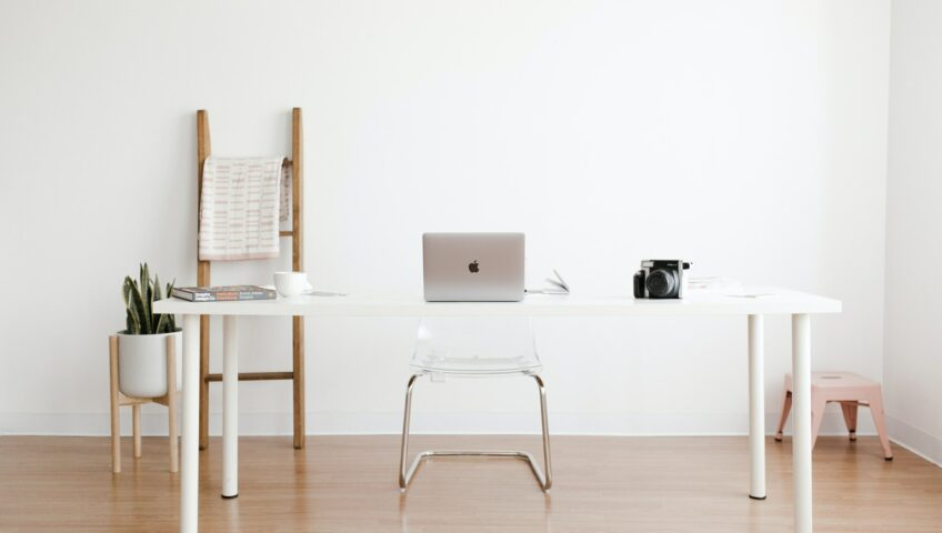 A Macbook sits on top of a white table along with a book, a white coffee cup, and a camera. Behind the table, there is a white chair, a potted plant, a wooden rack, and a small stool. The wall behind all of these things is plain white as well.