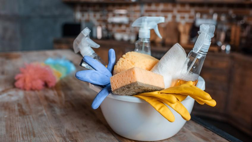 Cleaning supplies in a white bowl on a dusty wooden table. In the background, a blurred rustic kitchen is visible.