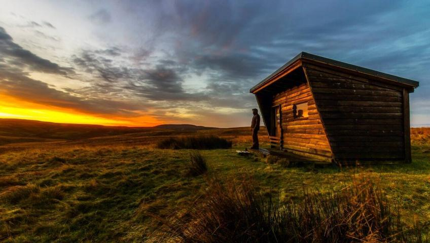 A man is standing outside of a wooden tiny house at sunset. The surrounding landscape seems to be grassy wide hills.