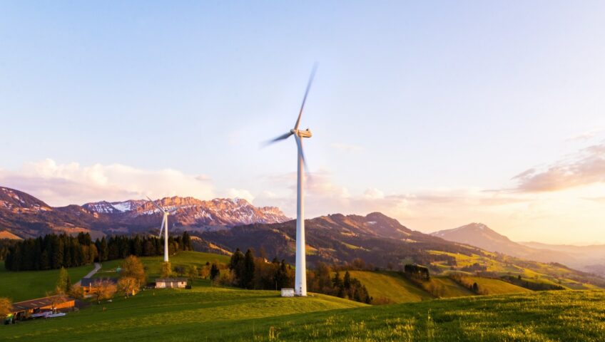 Two wind turbines are in motion atop grassy hills. Below them, there is a road and some smaller buildings and behind them, mountains are rising into the distance.
