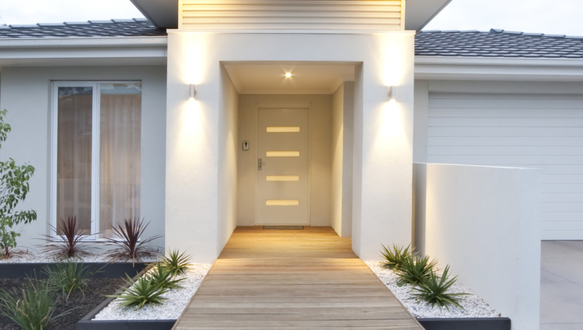 Exterior view of the front of a white, modern style home featuring a wooden plank leading to the brightly lit door surrounded by xeric plants set in white gravel.