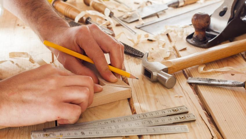 A carpenter adjusts two pieces of wood while holding a pencil in their hands. On the carpenter's workbench, various rulers, a hammer, wood shaving scraps, and other tools are visible.
