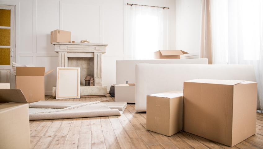 Cardboard boxes on a wooden floor in an otherwise empty room.