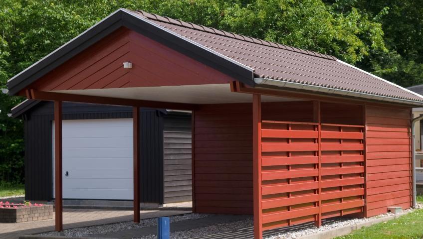 A wood-paneled carport painted barn red, with a brown shingled roof.