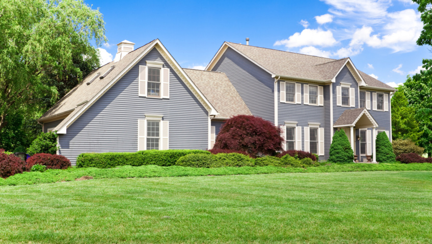 A single-family home with an attached mother-in-law suite, with trimmed shrubs and a vibrant green lawn out front.