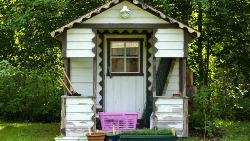 An outdoor gardening shed outfitted with electric lighting, a window, and storage.
