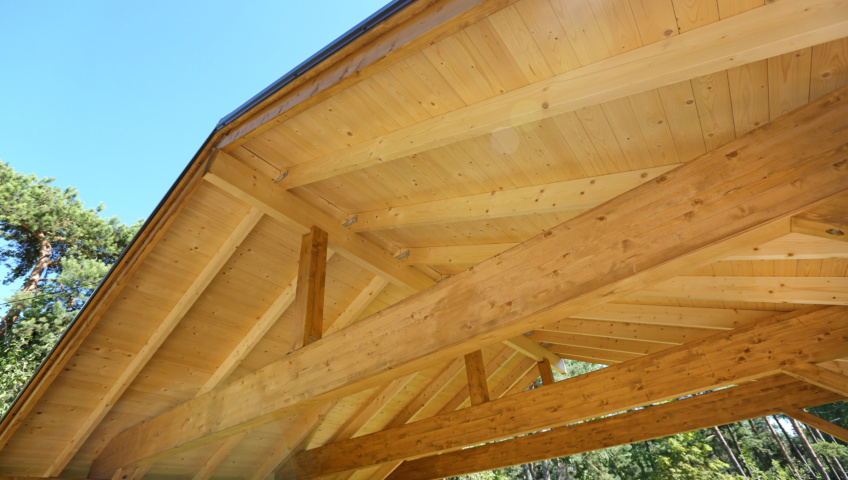 Interior view of the wooden roof and horizontal support beams of a carport under construction.